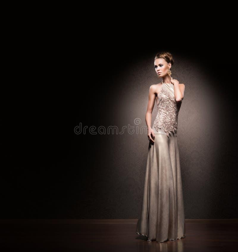 Mujer joven y atractiva que presenta en un vestido de noche fotografía de archivo