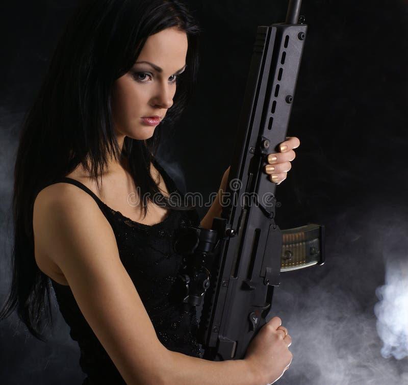 Mujer joven y atractiva que sostiene un rifle imagen de archivo