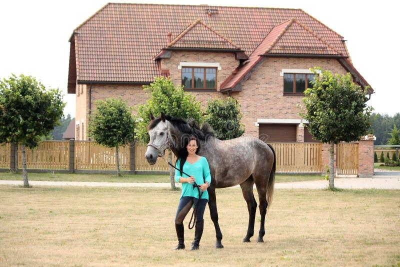 Mujer joven y caballo hermosos cerca de la cabaña foto de archivo