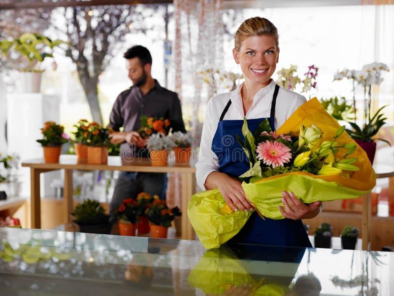 Mujer joven y cliente en departamento de flores fotografía de archivo libre de regalías
