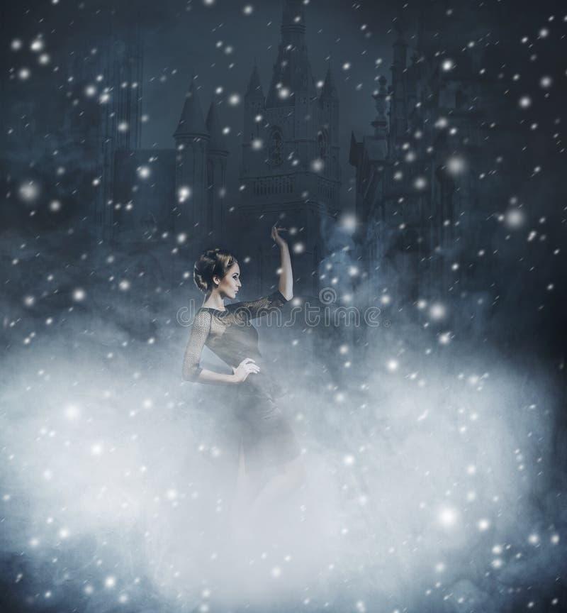Mujer joven y emocional en vestido de la moda en un fondo nevoso imagenes de archivo