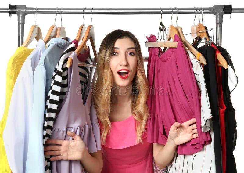 Mujer joven y estante hermosos con diversa ropa en el fondo blanco imagenes de archivo