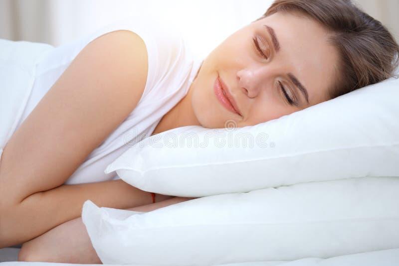 Mujer joven y feliz hermosa que duerme mientras que miente en cama comfortablemente y dichosamente sonríe fotos de archivo libres de regalías