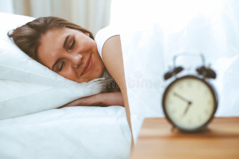 Mujer joven y feliz hermosa que duerme mientras que miente en cama comfortablemente y dichosamente sonr?e imagen de archivo libre de regalías
