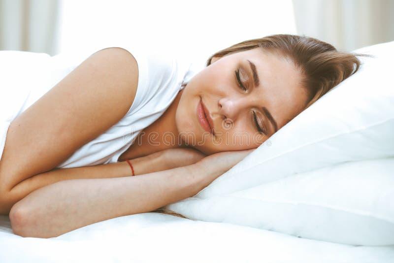 Mujer joven y feliz hermosa que duerme mientras que miente en cama comfortablemente y dichosamente sonr?e fotografía de archivo