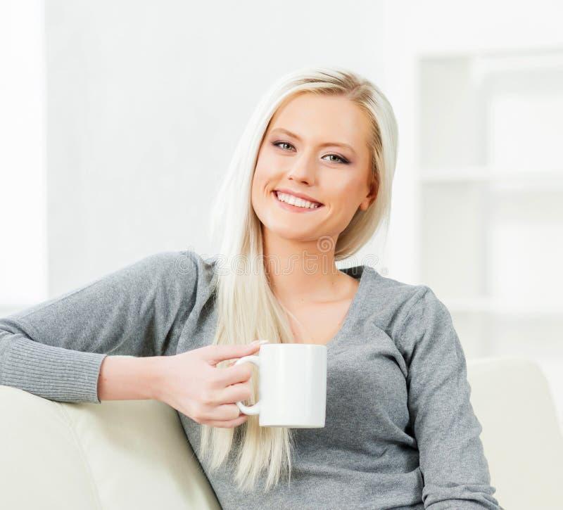Mujer joven y feliz que descansa sobre el sofá en casa con café fotos de archivo