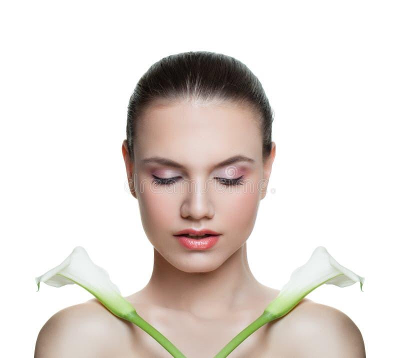 Mujer joven y flores perfectas aisladas en el fondo blanco Closeap modelo femenino hermoso de la cara Ojos cerrados foto de archivo libre de regalías