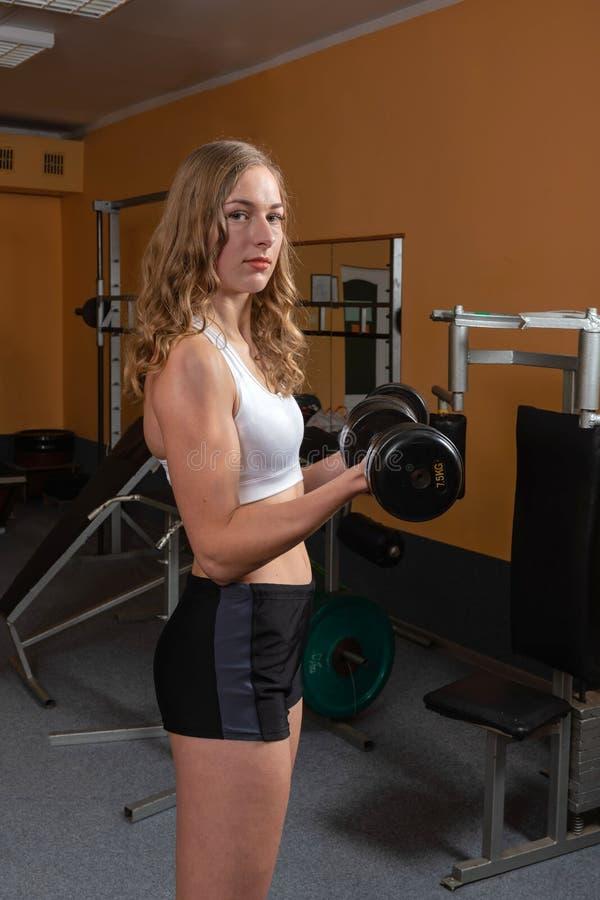Mujer joven y hermosa que se resuelve con pesas de gimnasia en gimnasio imagen de archivo