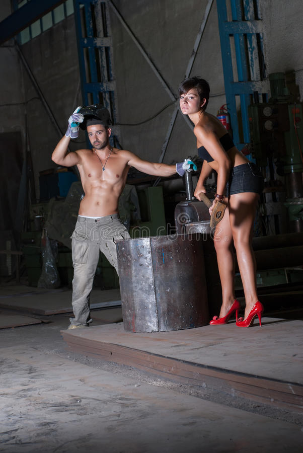 Mujer joven y hombre en fábrica imagen de archivo