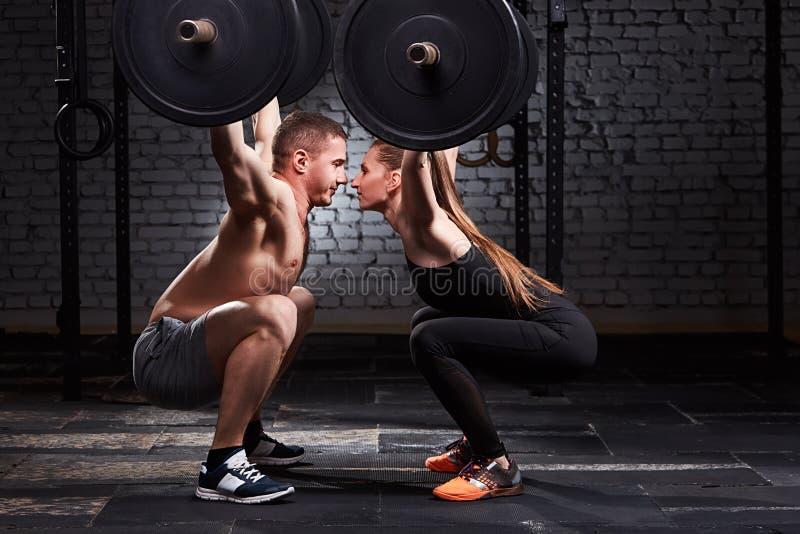 Mujer joven y hombre juguetones hermosos que levantan una pesa de gimnasia de posiciones en cuclillas enfrente de uno a contra la imagenes de archivo