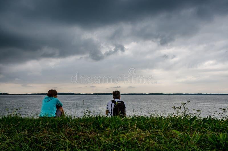 Mujer joven y hombre que se sientan en el campo delante de un lago en una tormenta de la tarde fotografía de archivo libre de regalías