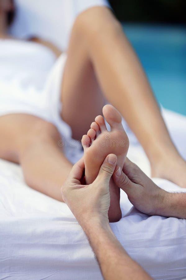 Mujer joven y masaje del pie foto de archivo