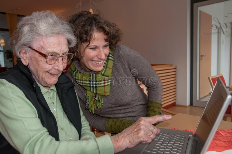 Mujer joven y mujer mayor con el cuaderno imagenes de archivo