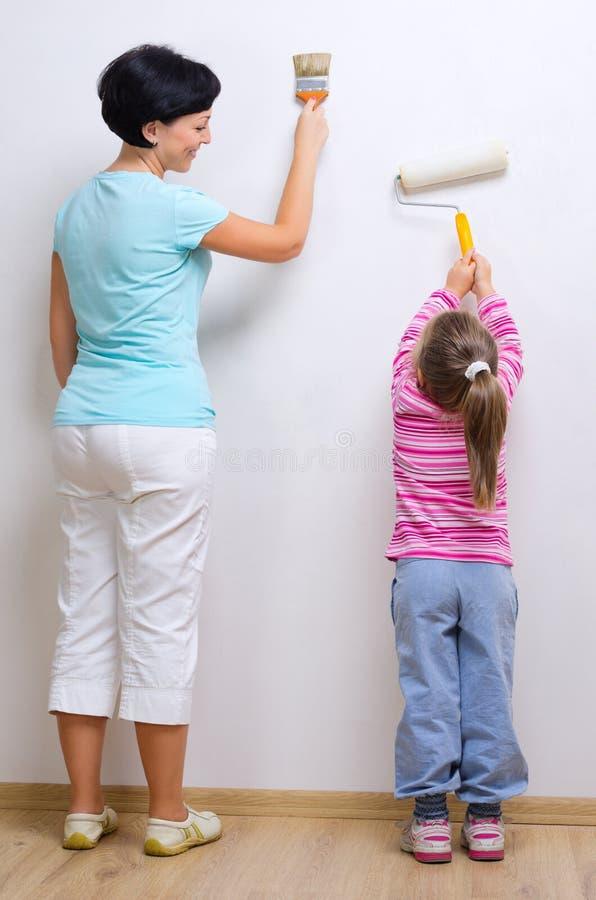 Mujer joven y niña con las herramientas de la pintura foto de archivo