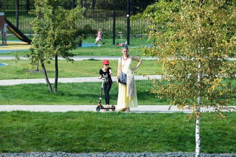 Mujer joven y niño en la vespa en el parque de Butovo, Moscú, Rusia foto de archivo