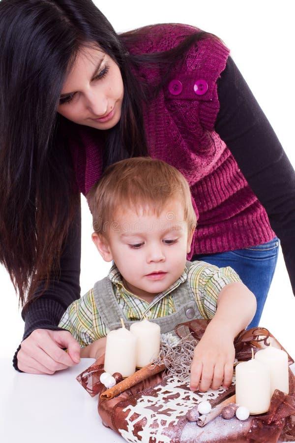 Mujer joven y niño pequeño con la guirnalda del advenimiento imagen de archivo