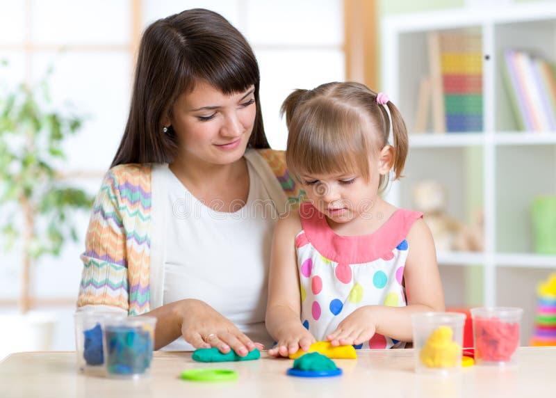 Mujer joven y niño que juegan con la arcilla colorida foto de archivo libre de regalías