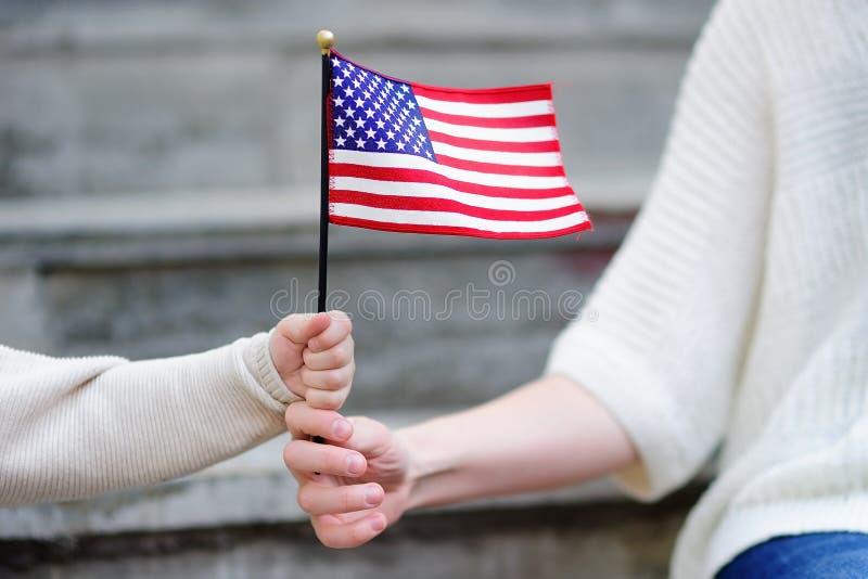 Mujer joven y pequeño niño que sostienen la bandera americana imagen de archivo