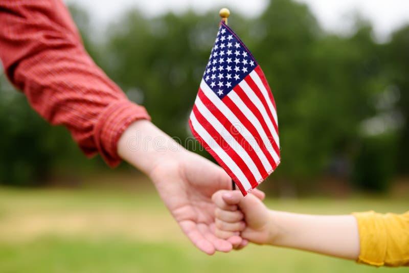 Mujer joven y peque?o ni?o que sostienen la bandera americana Concepto del D?a de la Independencia foto de archivo