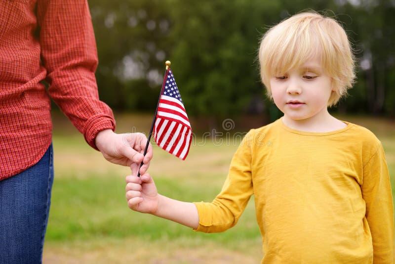 Mujer joven y peque?o ni?o que sostienen la bandera americana Concepto del D?a de la Independencia fotografía de archivo