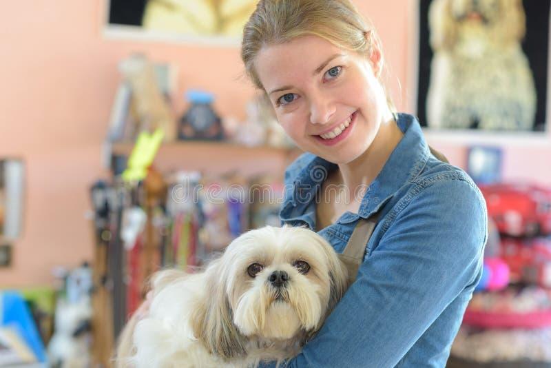 Mujer joven y perro del retrato en tienda del animal doméstico imagen de archivo