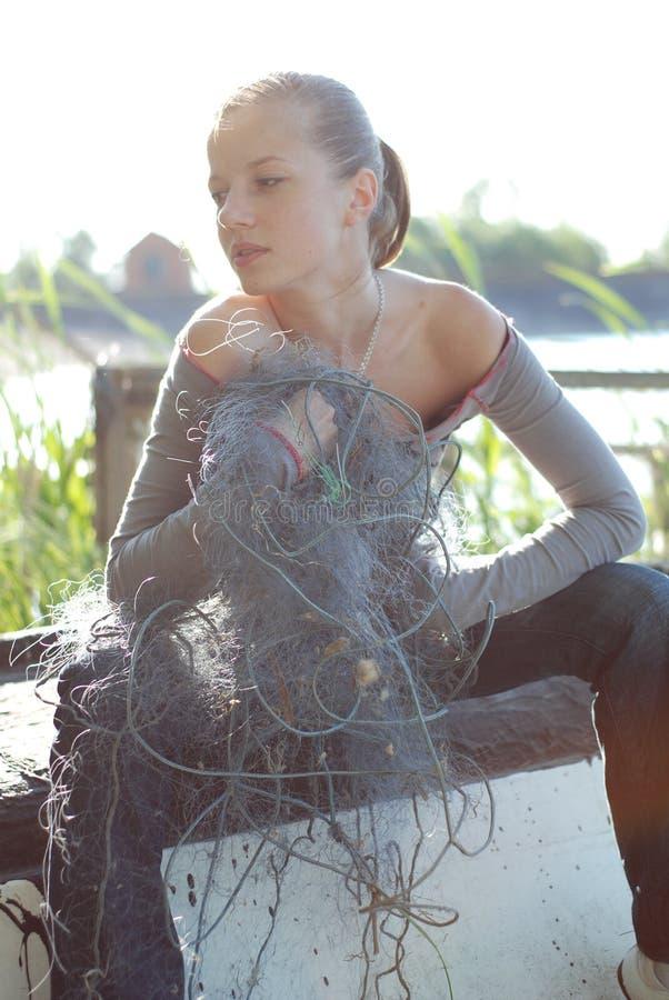 Mujer joven y red de pesca imagenes de archivo