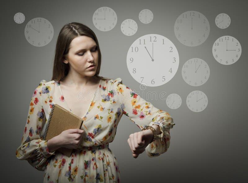 Mujer joven y reloj 11 p M foto de archivo