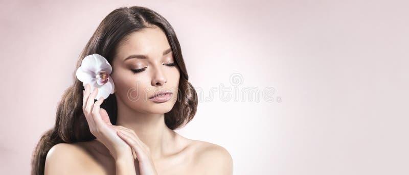 Mujer joven y sana con maquillaje ligero y flor de la orquídea en su pelo en fondo rosa claro imagenes de archivo