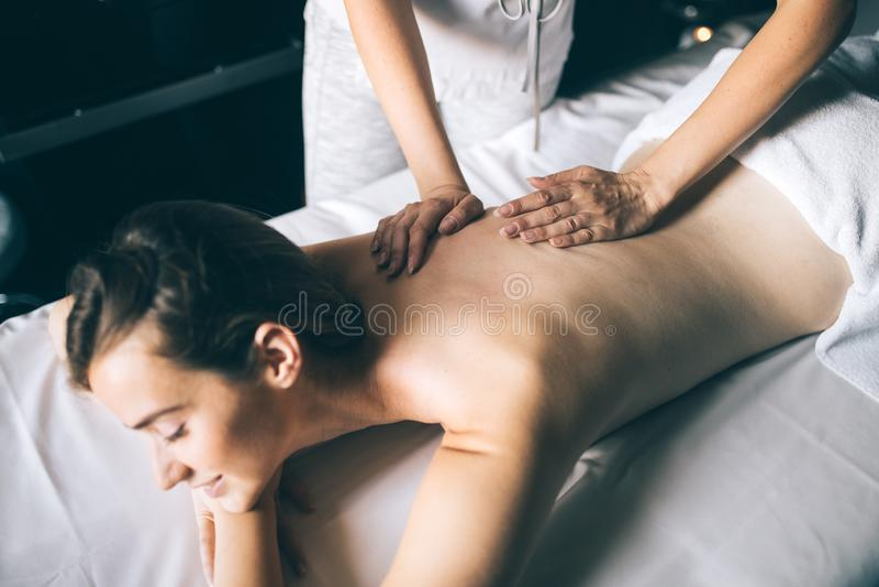 Mujer joven y sana en salón del balneario Terapia tradicional del masaje sueco imagen de archivo libre de regalías