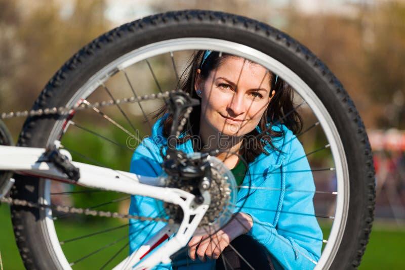 Mujer joven y su bici foto de archivo