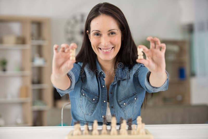 Mujer joven y tablero de ajedrez con ajedrez fotografía de archivo