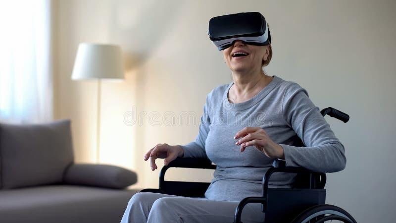 Mujer jubilada en las gafas y el juego del goce que llevan, tecnología del vr de la silla de ruedas foto de archivo