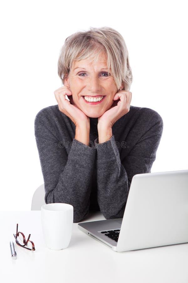 Mujer jubilada moderna con un ordenador portátil foto de archivo libre de regalías