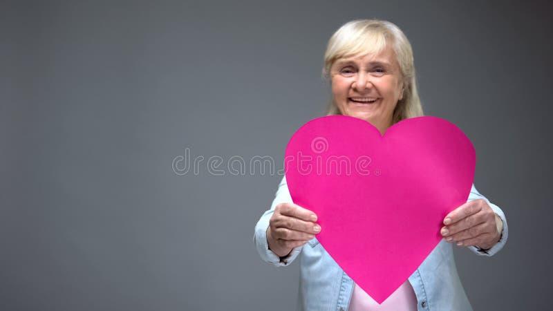 Mujer jubilada optimista que muestra el corazón rosado grande, servicios de la clínica de la cardiología foto de archivo libre de regalías