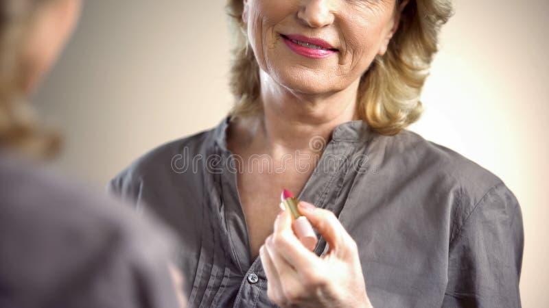 Mujer jubilada que aplica el lápiz labial rosado delante del espejo, cosméticos de la anti-edad foto de archivo