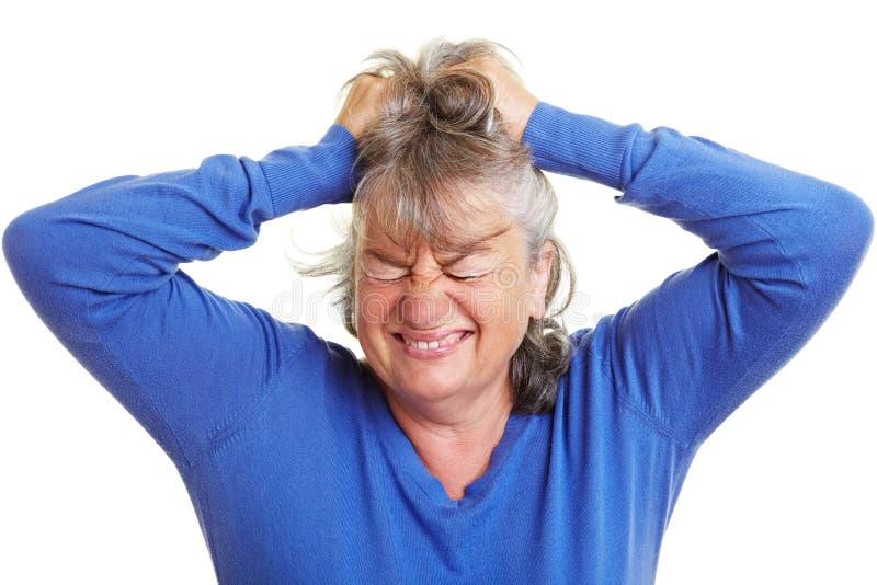 Mujer jubilada que tira de su pelo imagenes de archivo