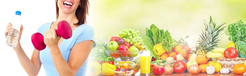 Mujer juguetona con las frutas y pesa de gimnasia foto de archivo