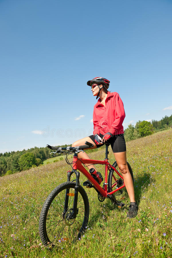 Mujer juguetona joven en la bici de montaña fotos de archivo