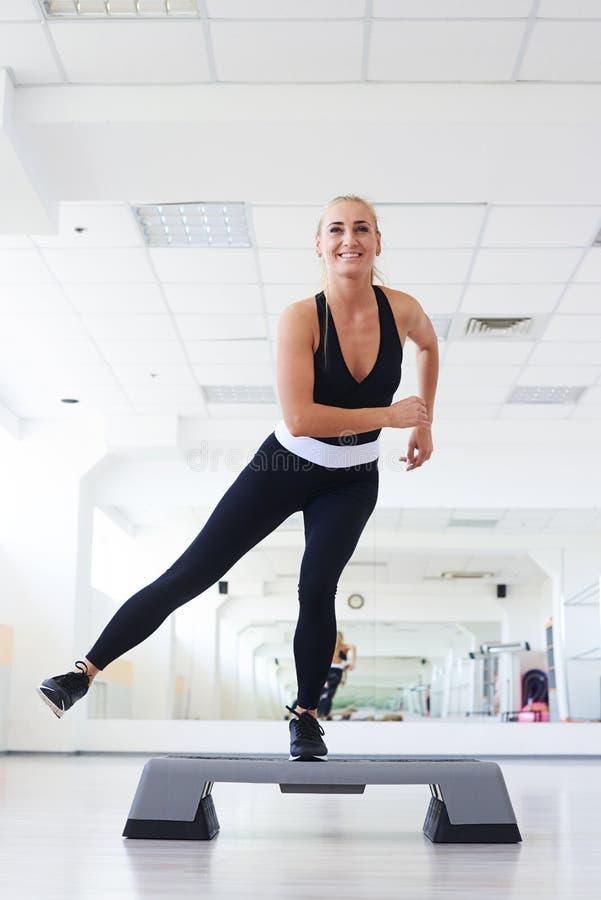 Mujer juguetona joven que ejercita en gimnasio usando la plataforma del paso foto de archivo