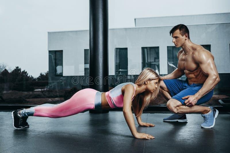Mujer juguetona que hace el ejercicio del tablón que entrena detrás y los músculos de la prensa con el instructor Poder de la fue fotografía de archivo libre de regalías
