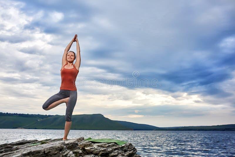Mujer juguetona que se opone en la roca y la yoga practicante al río imagen de archivo
