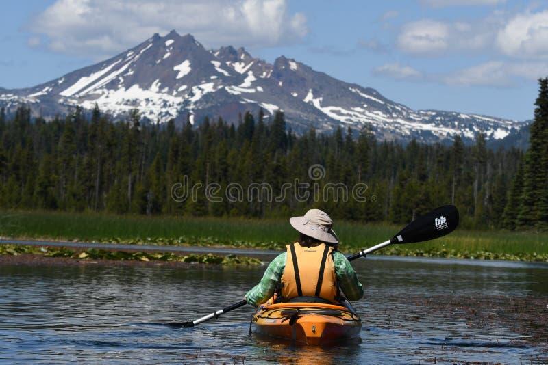 Mujer kayaking hacia pico de montaña nevoso imágenes de archivo libres de regalías