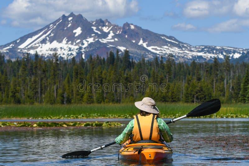 Mujer kayaking hacia pico de montaña nevoso fotografía de archivo libre de regalías