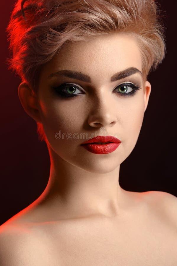 Mujer labiada roja rubia joven hermosa que presenta en el rojo artístico l fotos de archivo libres de regalías