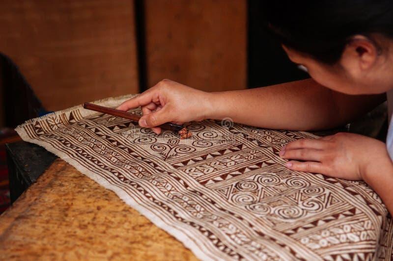 Mujer laosiana hacer la pintura de la tela del batik fotos de archivo