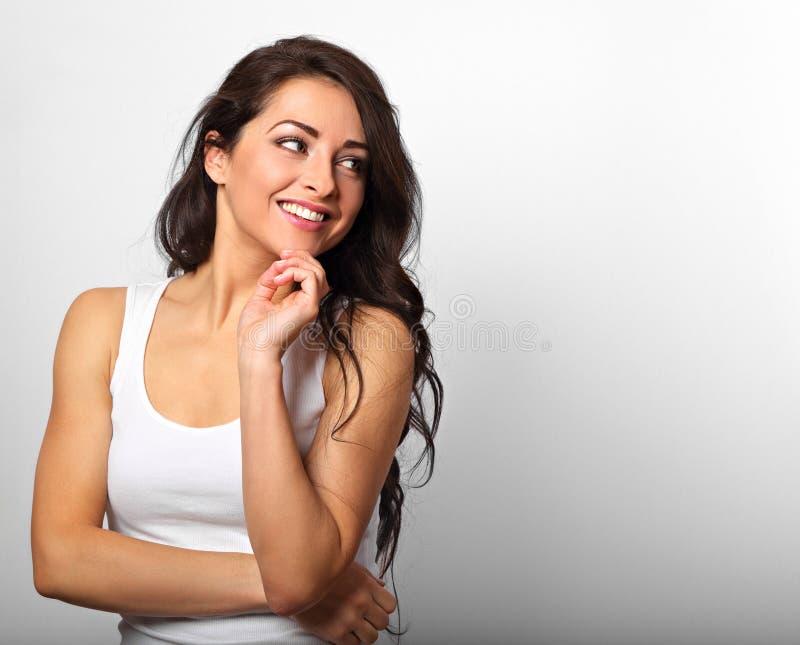 Mujer larga feliz de pensamiento hermosa del peinado en la camisa blanca y fotografía de archivo libre de regalías