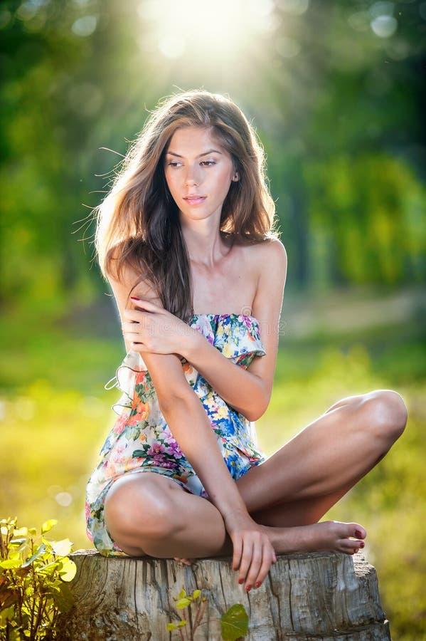 Mujer larga hermosa joven del pelo que lleva un vestido multicolor que presenta en un tocón foto de archivo
