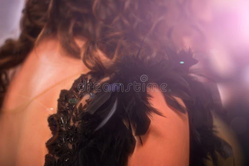 Mujer larga magnífica del pelo que lleva la pluma negra del vestido de noche en la opinión de la parte posterior de la oscuridad imagenes de archivo
