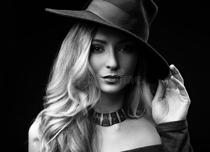 Mujer larga rubia del estilo de pelo del maquillaje atractivo presentando en el sombrero de la moda imagen de archivo libre de regalías