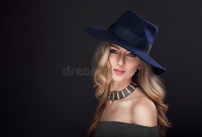 Mujer larga rubia del pelo del maquillaje atractivo del encanto que presenta en sombrero de la moda imagenes de archivo